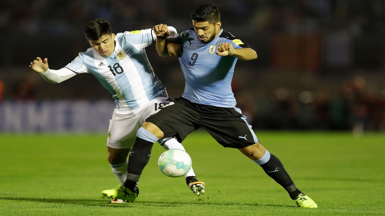 In this Thursday, Aug. 31, 2017 file photo, Uruguay's Luis Suarez, right, fights for the ball with Argentina's Marcos Acuaa during a 2018 World Cup qualifying football match in Montevideo, Uruguay.