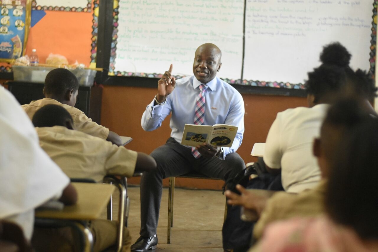Elon Parkinson Group Regional Communications Manager reads to students of St Benedict's Primary in observance of Read Across Jamaica Day on Tuesday. (Photo: Marlon Reid).