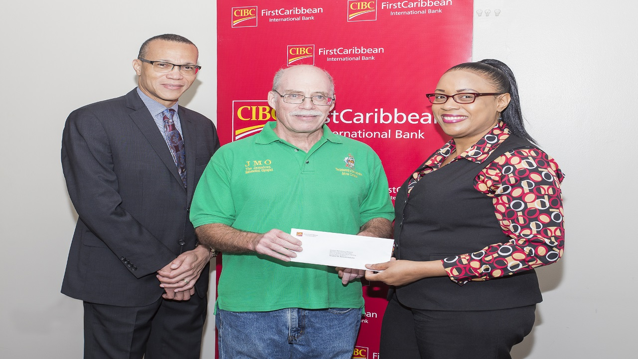 Douglas Cupidon (left), Head of Corporate & Investment Banking, CIBC FirstCaribbean International Bank, and Keisha Bennett-Henry (right), Client Service Officer presented the bank's cheque to Raymond McEachern, of the Jamaica Mathematical Olympiad.