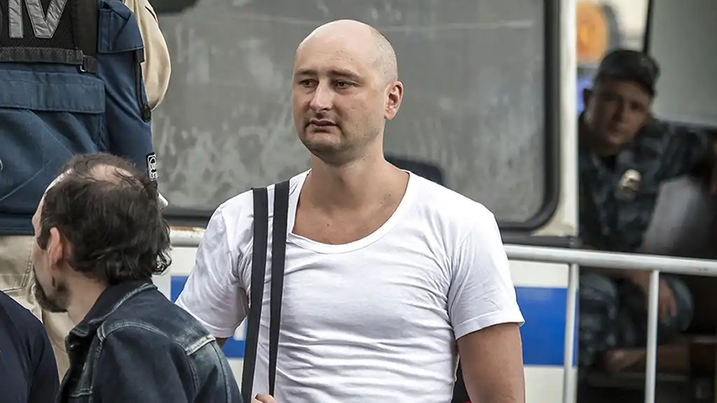 In this photo taken on Friday, May 31, 2013, Arkady Babchenko, 41, who had been scathingly critical of the Kremlin in recent years, stands at a police bus during an opposition rally in Moscow, Russia. (AP Photo/Alexander Baroshin)