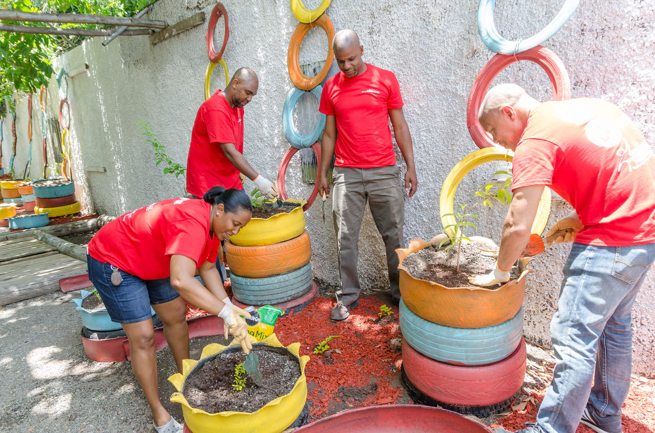 Andrew Leo-Rhynie (far right), General Manager of GK General Insurance; Tanketa Chance-Wilson, General Manager of Grace & Staff Community Development Foundation; and Steven Whittingham (second left), Managing Director of GK Capital Management; take part in planting activities at the newly erected peace garden in memory of a slain student at the Holy Family Infant & Primary School last Wednesday. The school's principal, Christopher Wright, looks on.