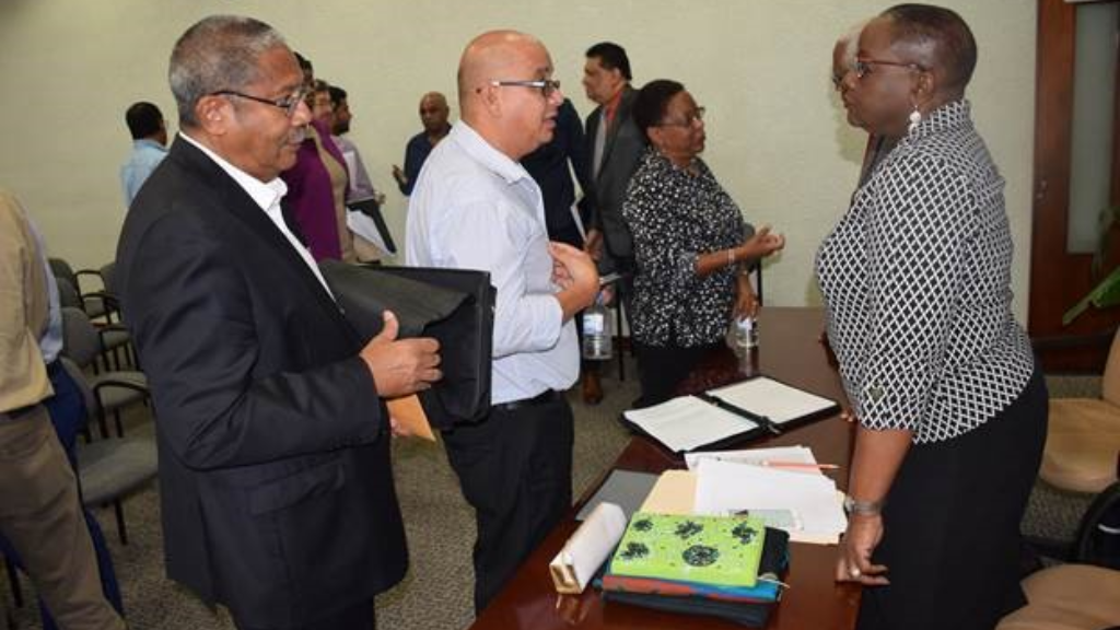 Planning and Development Minister Camille Robinson-Regis chats with contractors following a meeting on Tuesday over outstanding sums owed by the Education Facilities Company Limited (EFCL).