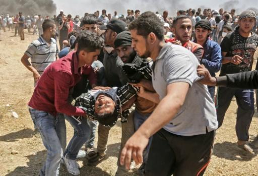Un Palestinien blessé par des tirs israéliens est évacué par d'autres manifestants, le 14 mai 2018 dans la bande de Gaza, à la frontière avec Israël/ AFP