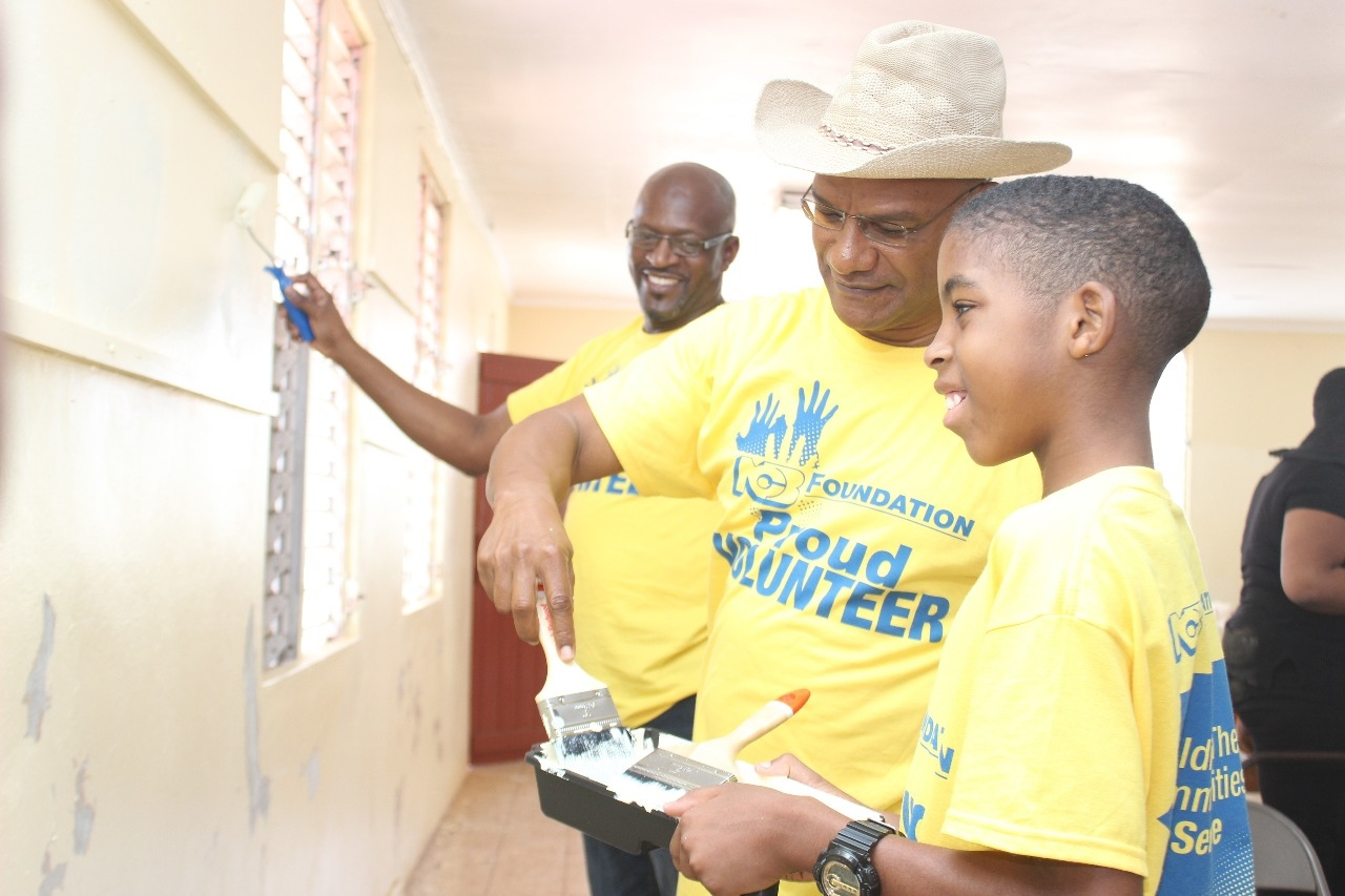 David Wilson, N.C.B.F. Director, looks on as Member of Parliament Peter Bunting shows a young lad the many tips and tricks for painting walls. Bunting was a proud volunteer along with many other volunteers and NCB staff and executives who showed support for Labour Day projects held at the Knockpatrick campus of the Caribbean Christian Centre of the Deaf (CCCD) in Manchester.