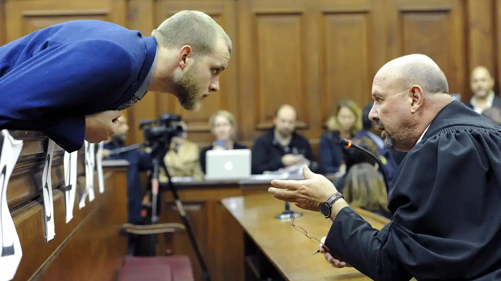 Henri van Breda, left, talks to one of his legal adviser, Piet Botha, right, in the HIgh Court in Cape Town, South Africa, Monday, May 21, 2018 as he awaits the verdict in his murder, and attempted murder trial. (AP Photo/Nasied Manie)