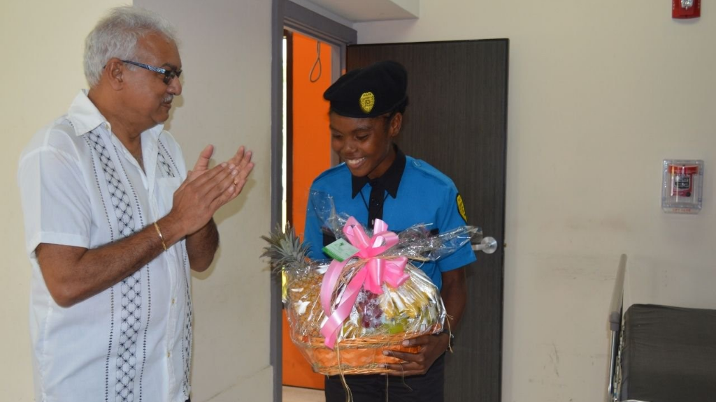 Dasell George receives a hamper of appreciation from Minister of Health Terrence Deyalsingh