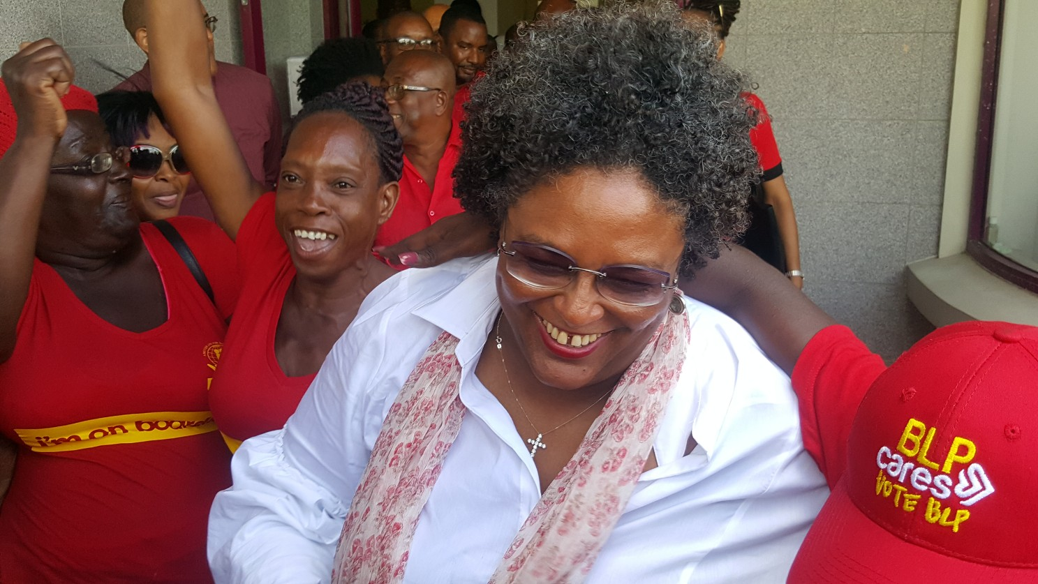 Mia Mottley leading the candidates out into the sea of red shirts after paying their deposits.