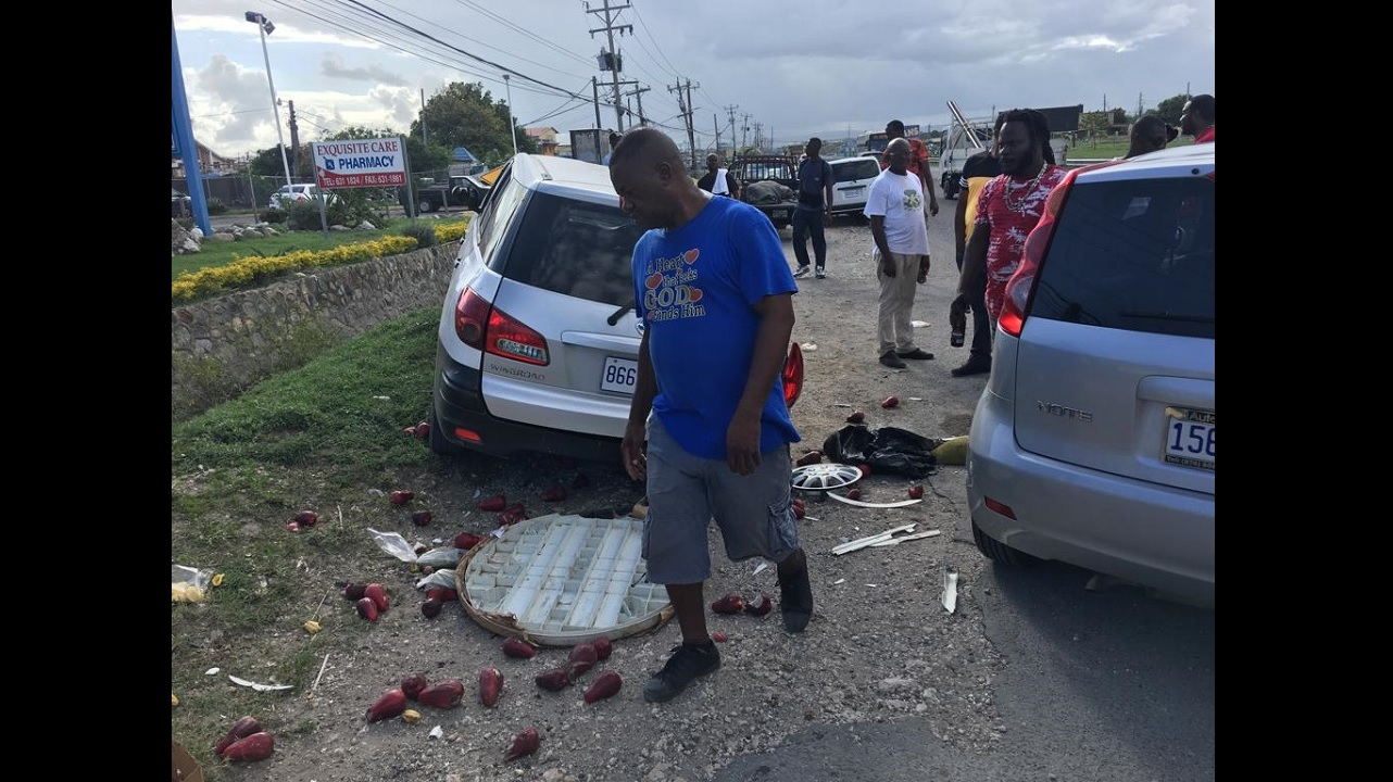Onlookers at the scene of the accident along Port Henderson Road in Portmore, St Catherine on Thursday.