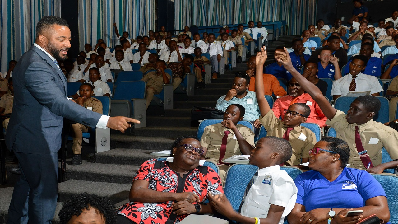 Presenter Troy Kemp interacts with a participant during the question and answer segment at the J Wray and Nephew Foundation (JWNF) 'Spotlight Session': Focus on Boys conference at the Courtleigh Auditorium recently. More than 300 boys from high schools in Kingston and St Andrew, Clarendon and St Elizabeth were in attendance.