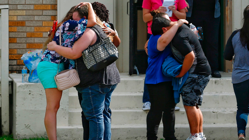 People embrace outside the Alamo Gym where students and parents wait to reunite following a shooting at Santa Fe High School Friday, May 18, 2018, in Santa Fe, Texas.