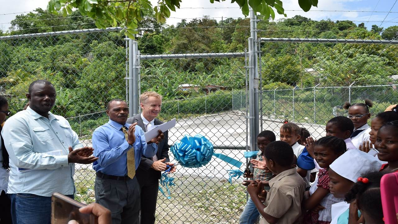 Acting USAID Mission Director Andrew Colburn (third from left) cuts the ribbon officially commissioning the refurbished water harvesting facility to the applause of (left) Councillor Stephen Williams Councillor for the St. Margaret's Bay Division, President of the Rock Hall Benevolent Society, Byron Papley and students from the Rock Hall Primary School.