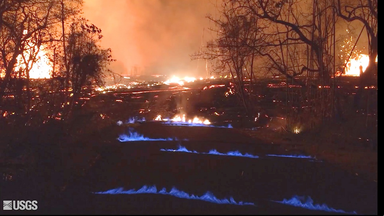 (Image: AP: This USGS photo shows blue burning flames of methane gas erupting through cracks on the island of Hawaii on 23 May 2018)