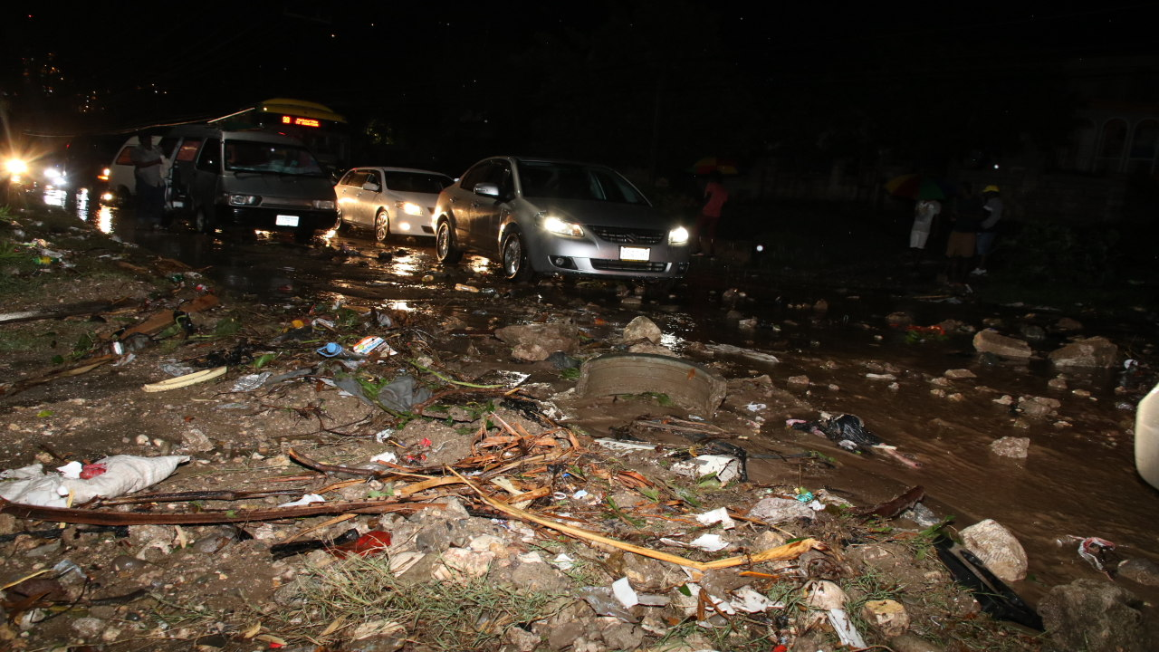 Motorists travel through mud and debris along the Harbour View main road on Sunday night. (PHOTOS: Llewellyn Wynter)