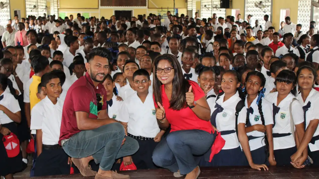Photo Caption: (L-R) Devendra Bishoo, Bowler for the Guyana Amazon Warriors spent some time with Vidya Sanichara, Communications Manager at Digicel Guyana and students at the Berbice High School getting them excited about the upcoming Digicel Youth Cricket Series.