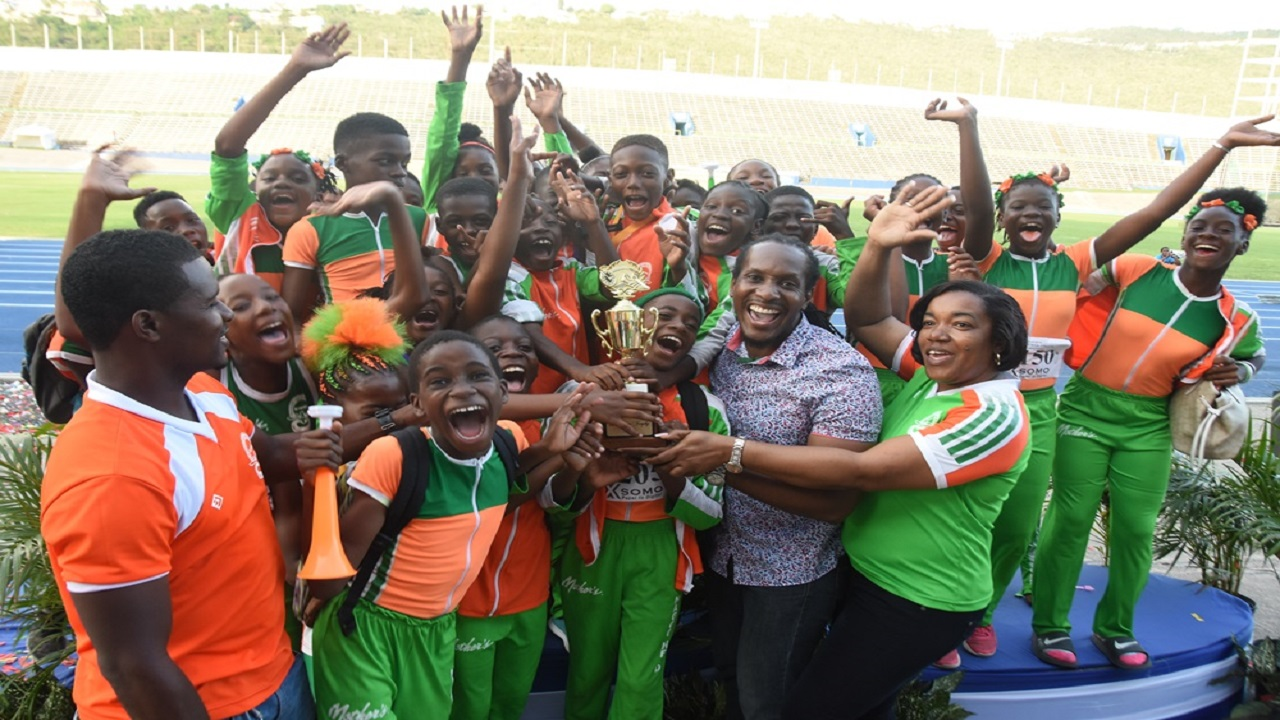 Members of Naggo's Head Primary celebrate after accepting the winning trophy from  State Minister in the Ministry of Culture, Gender, Entertainment and Sport, Alando Terrelonge (2nd right)  on Saturday's fourth and final day of the 38th INSPORTS Primary School Athletics Championships at the National Stadium.