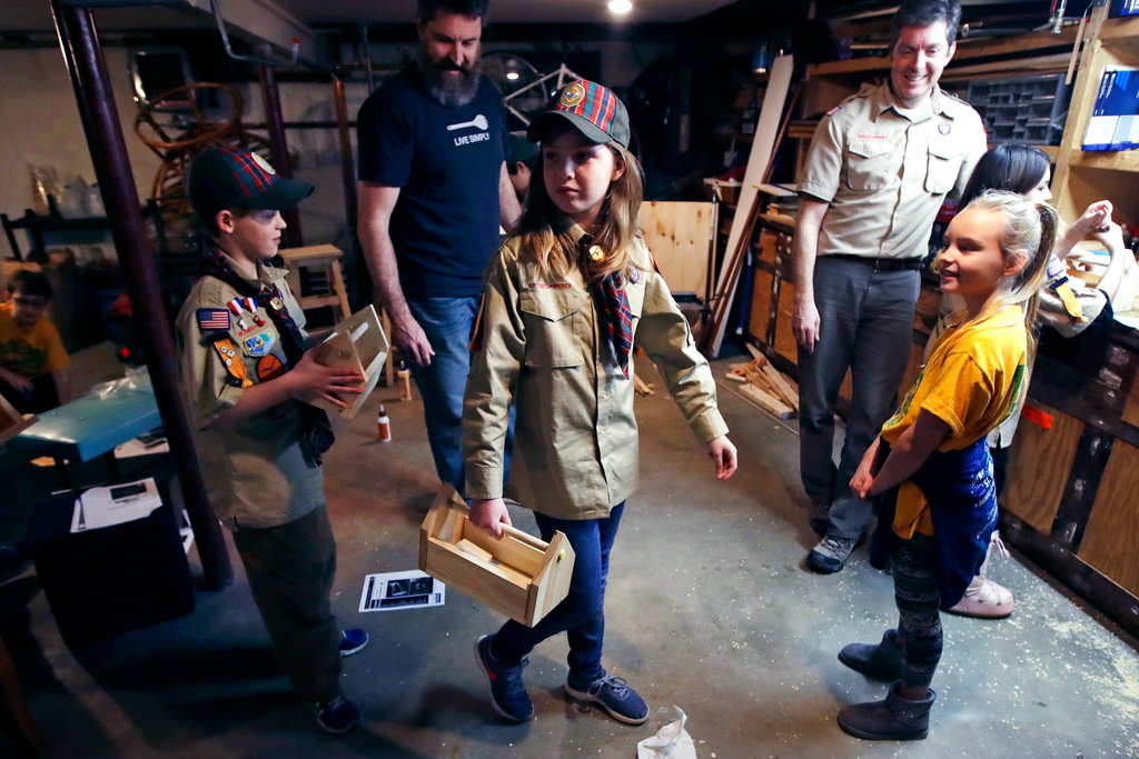 Tatum Weir, center, carries a tool box she built as her twin brother Ian, left, follows after a Cub Scout meeting in Madbury, N.H. (AP Photo/Charles Krupa, File)