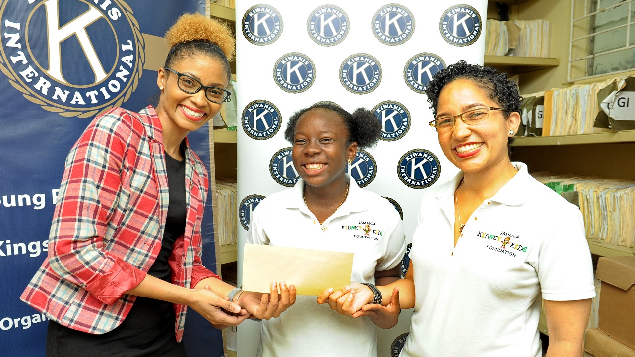 (L-R) President elect of Kiwanis Club of Young Professionals Kingston, Jamaica, Naketa West is a cheerful giver as she hands over a cheque to the equally pleased Angelee Bennett, a beneficiary of the Jamaica Kidney Kids Foundation (JKKF) and Erin Hayle, coordinator of JKKF.