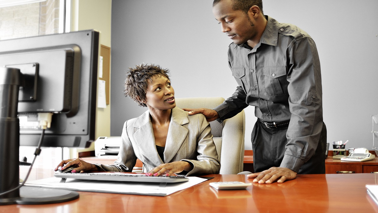 Stock image of a man resting his hand on a woman's shoulder in an office.