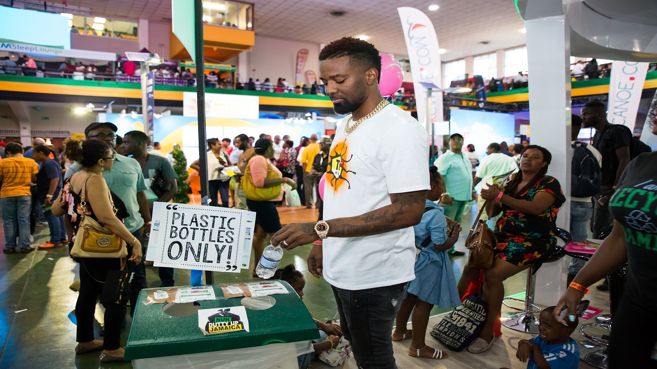 Recording artiste Konshens makes use of one of the recycling bins provided by Wisynco Eco at Expo Jamaica.
