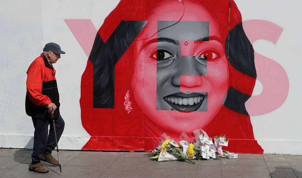 A man walks past a mural showing Savita Halappanavar, a 31-year-old Indian dentist who had sought and been denied an abortion before she died after a miscarriage in a Galway hospital.