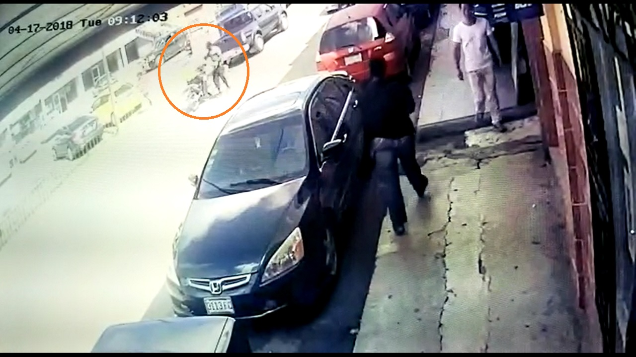 The circled area of the screenshot shows a machete-wielding man chopping the cop while the lawman drives his bike.