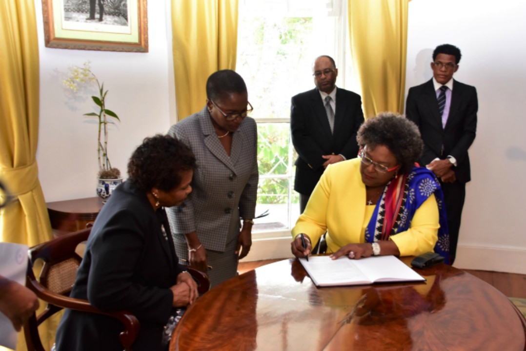 Prime Minister, Mia Mottley (right) signing the Official Register in the presence of Governor General Dame Sandra Mason (right) and Dame Sandra's Private Secretary, Sandra Watkins at Government House. 