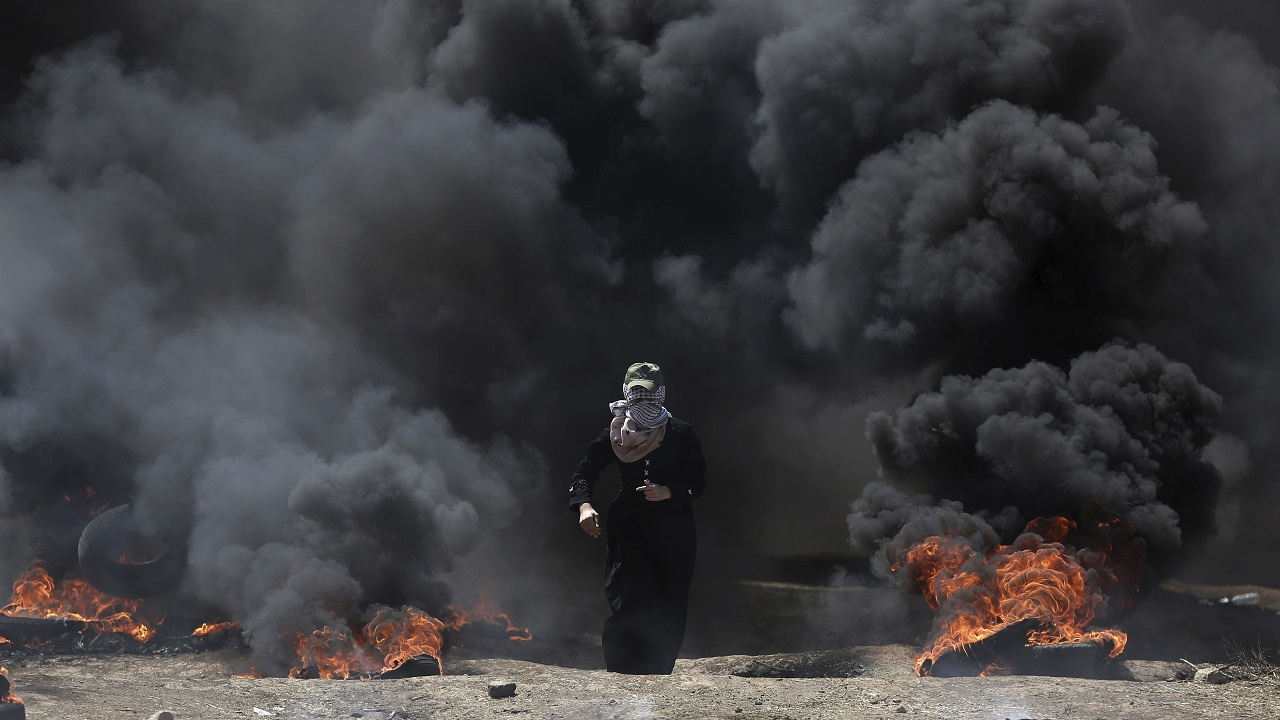 (Image: AP: A Palestinian woman walks through black smoke from burning tires during a protest in Gaza on 14 May 2018)