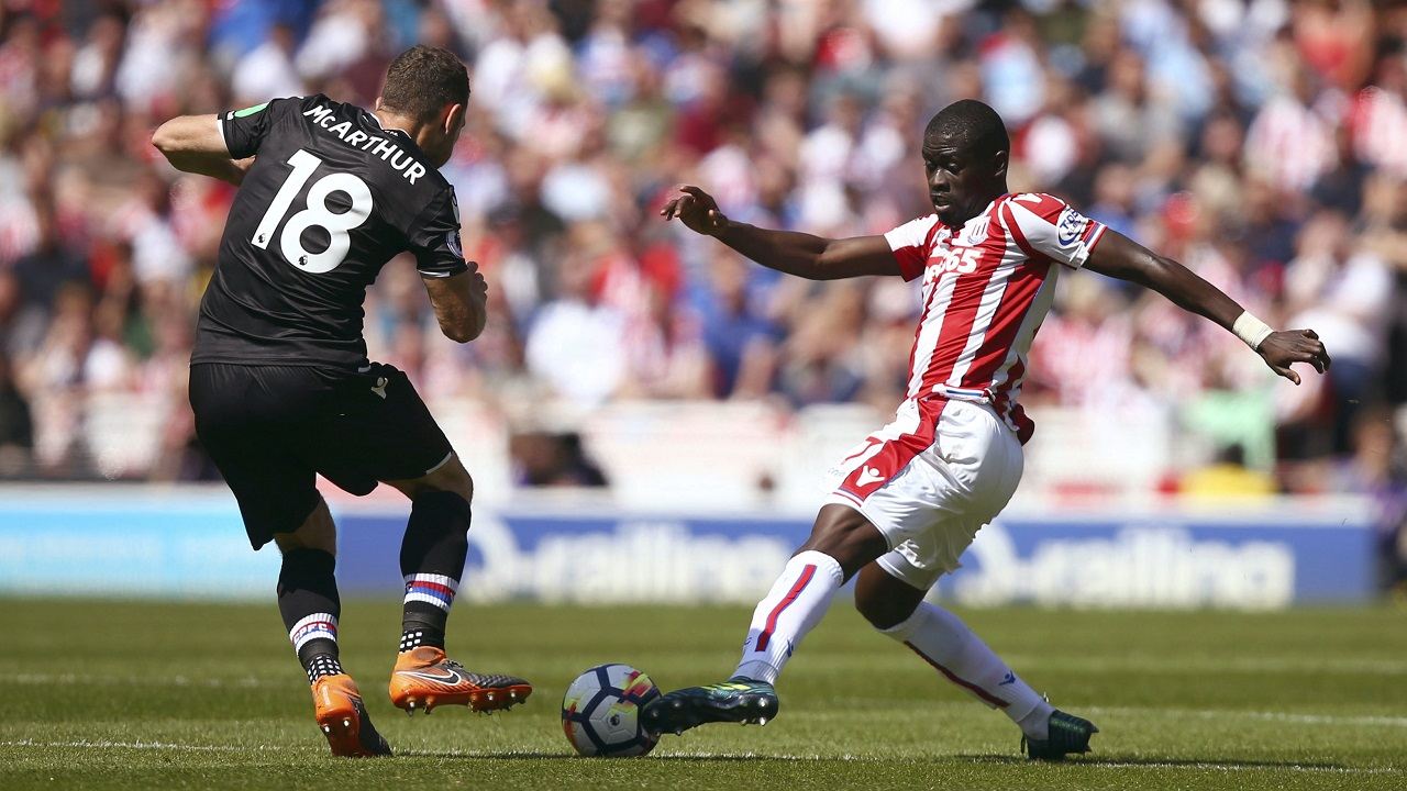 Crystal Palace's James McArthur, left, and Stoke City's Badou Ndiaye battle for the ball during their English Premier League football match, at the bet365 Stadium, in Stoke, England, Saturday May 5, 2018.