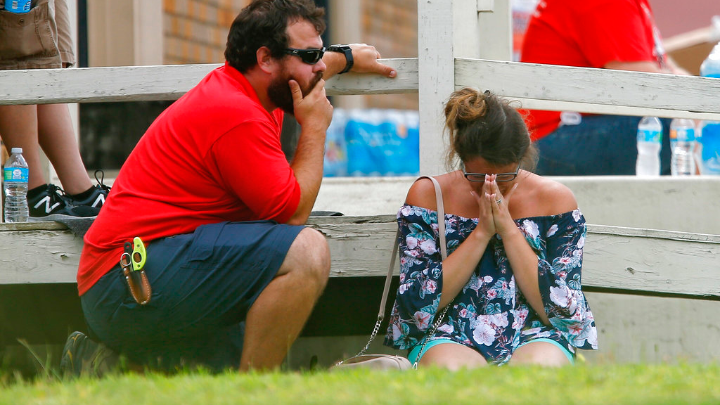 A woman prays in the grass outside the Alamo Gym where parents wait to reunite with their kids following a shooting at Santa Fe High School Friday, May 18, 2018, in Santa Fe, Texas