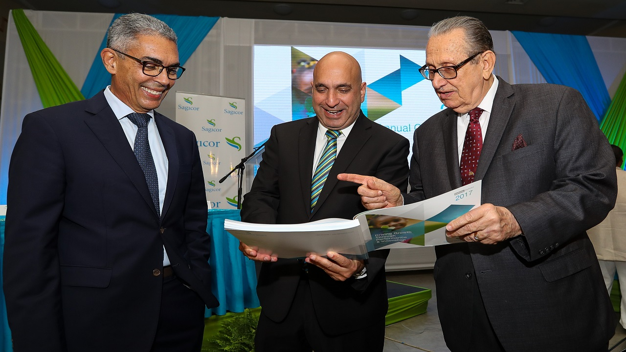 President and CEO of Sagicor Group Jamaica, Christopher Zacca (centre), share some insights from the 2017 Annual Report to his predecessor Richard Byles (left), Chairman of Sagicor Group Jamaica and R. Danny Williams, Director Emeritus of Sagicor Group Jamaica.