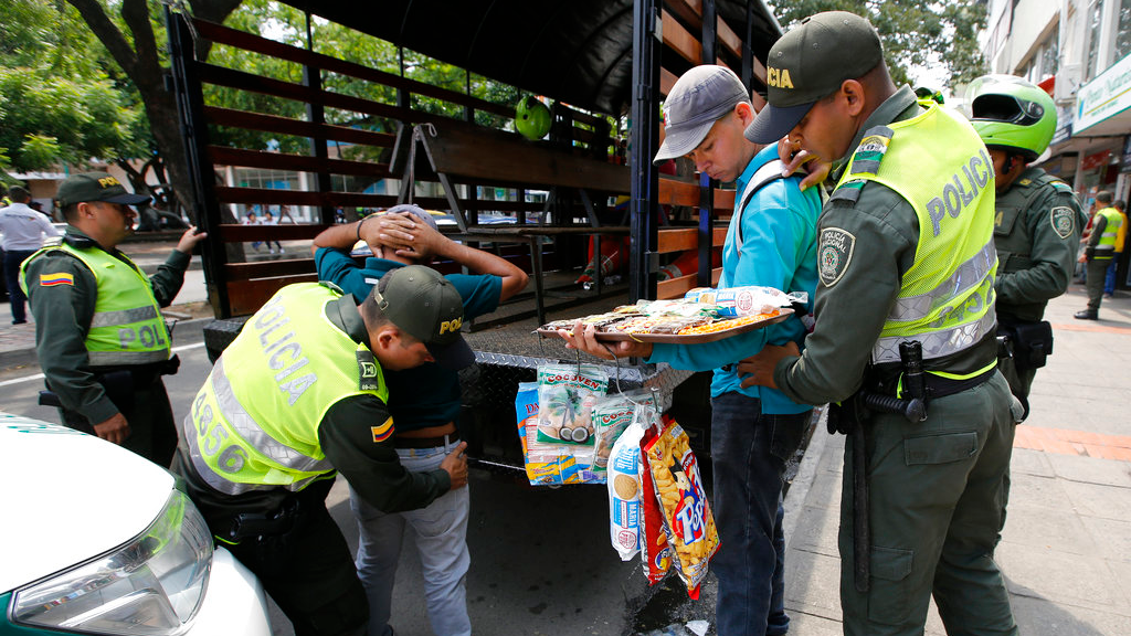 Colombian police officers detain Venezuelan migrants who do not have no ID's and permits to sell products, in Cucuta, Colombia. Officially, Colombia deports few Venezuelan migrants: 442 have been removed from the country so far in 2018, according to government figures. (AP Photo/Fernando Vergara, File)