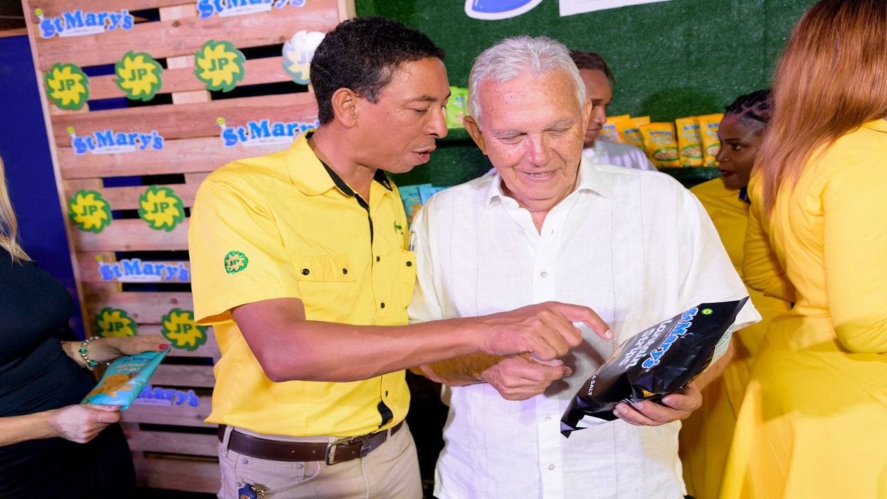Charles Johnston  Chairman of the Jamaica Producers Group (right) examines one of the St Mary's chips with David Martin (left), Managing Director, JP Tropical Group.
