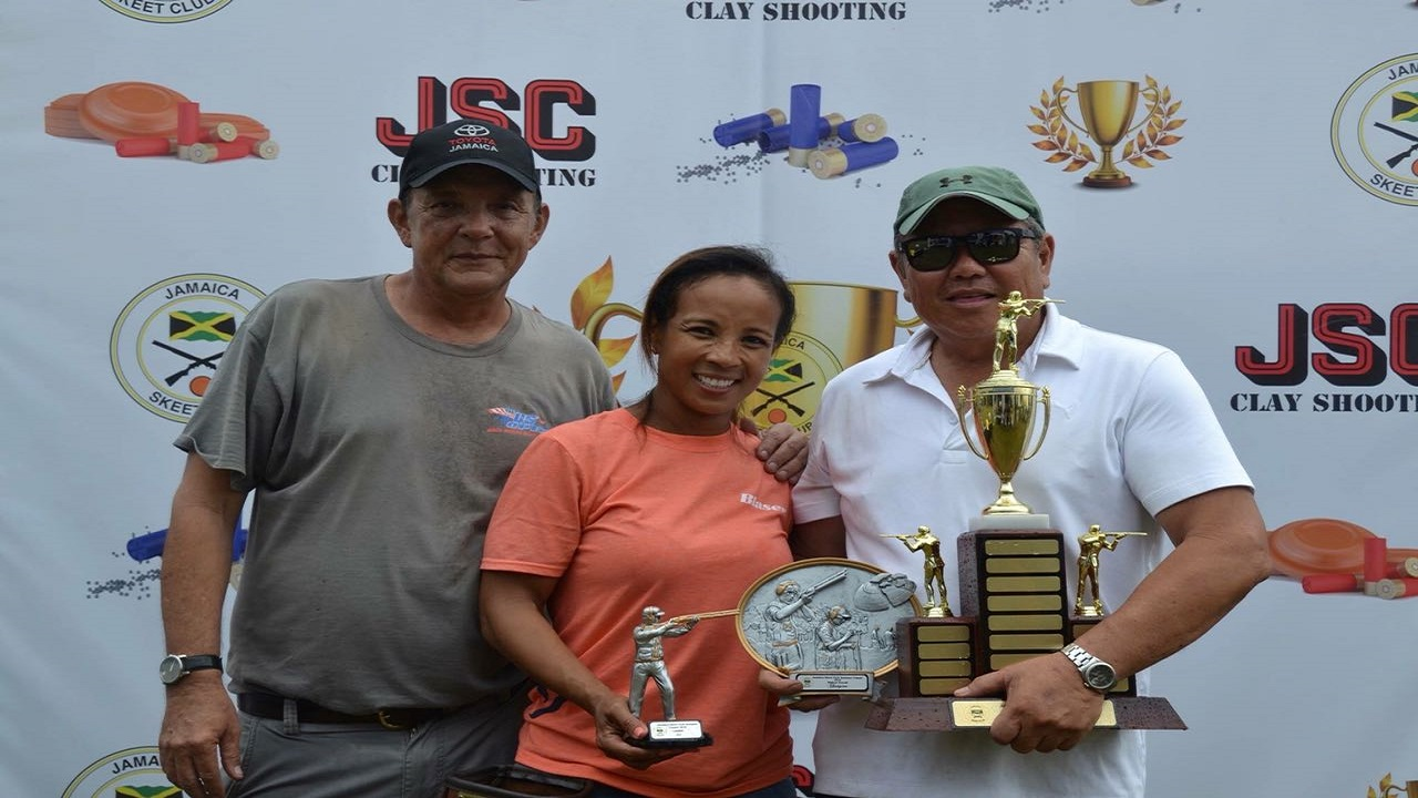 Robert Yap Foo (right) and Wendy McMaster (centre) pose with the main prizes following the Jamaica Skeet Club's inaugural Summer Sporting Clays Classic  at the Woodleigh Shooting Range in Clarendon on Sunday. At left is Evan Thwaites, president of the Jamaica Skeet Club.