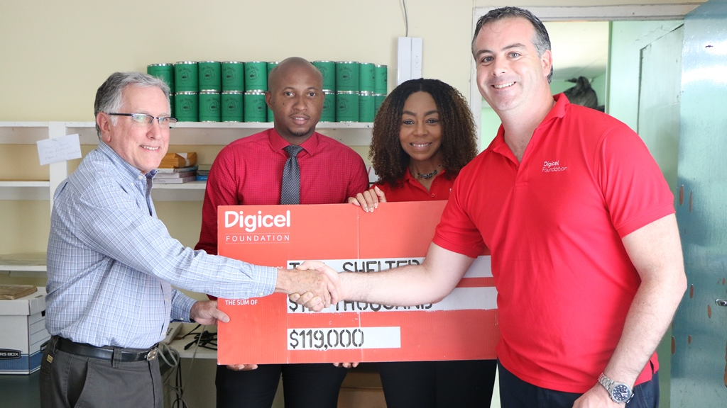 John Delves, Director and Penny Gomez, CEO of the Digicel Foundation presents the cheque to Anthony Inglefield, Chairman at The Shelter (left) as Andreas Isaacs (2nd from left) looks on