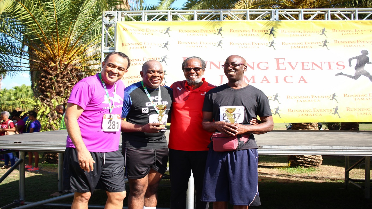 Everyone's A Winner race patron Senator Dr Floyd Morris (second left) and his guide Donovan Jacas (right) collect their second-place trophies in the Jamaica Moves Top VIP (visually impaired person) and Guide Duo race category from Minister of Health, Dr Christopher Tufton (left) and Alfred 'Frano' Francis, director of Running Events Ltd at the prize-giving ceremony for the first leg of the 5K and 10K event on Sunday at Hope Gardens.
