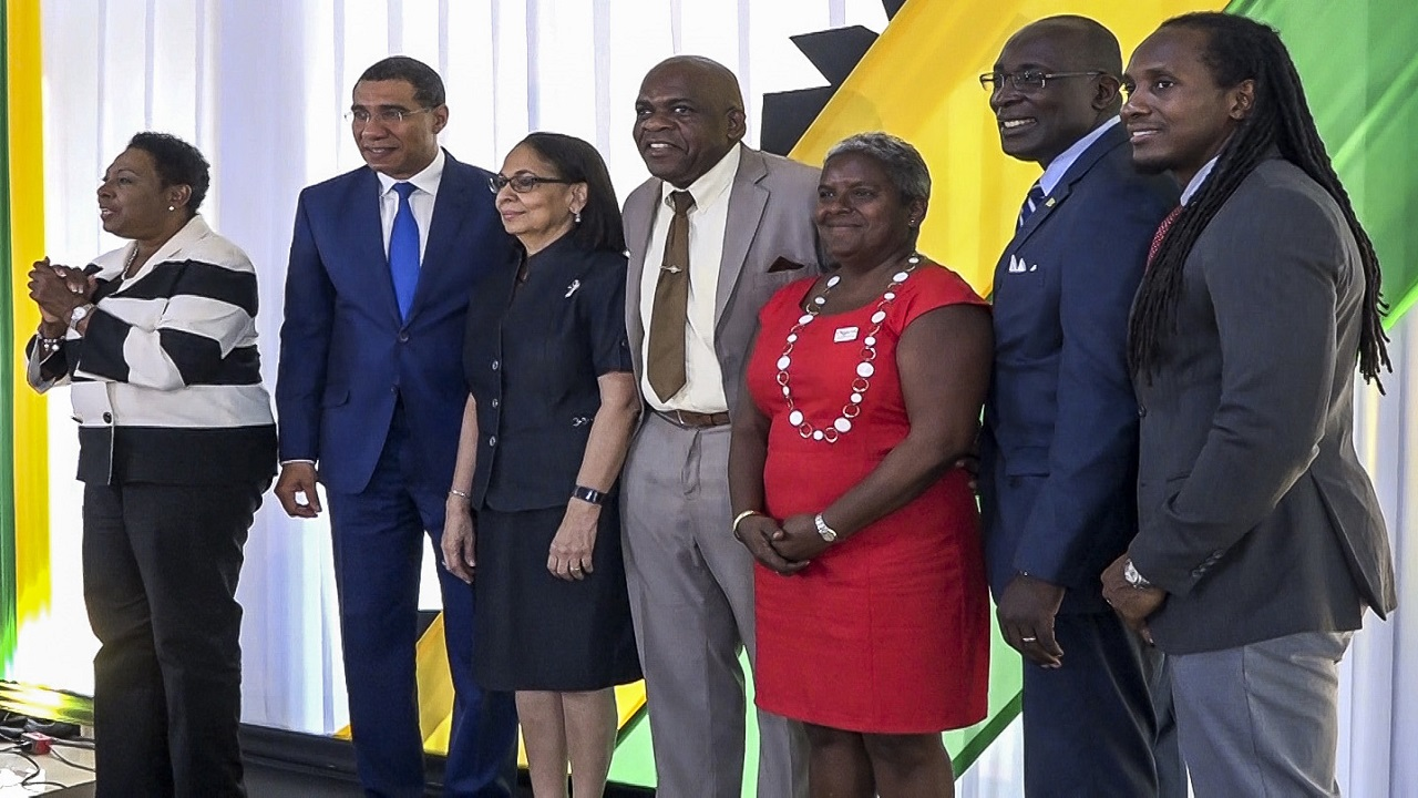 Olivia Grange, Minister of Culture, Gender, Entertainment and Sport (left), makes a point at the launch of Workers' Week and Labour Day on May 1 at the Office of the Prime Minister. Sharing the moment are (l-r) Prime Minister Andrew Holness; Minister of Labour and Social Security, Shahine Robinson; Senator Floyd Morris; Acting Head of the Digicel Foundation,  Karlene Dawson; Minister of Education, Youth and Information, Senator Ruel Reid; and State Minister for CGES, Alando Terrelonge.