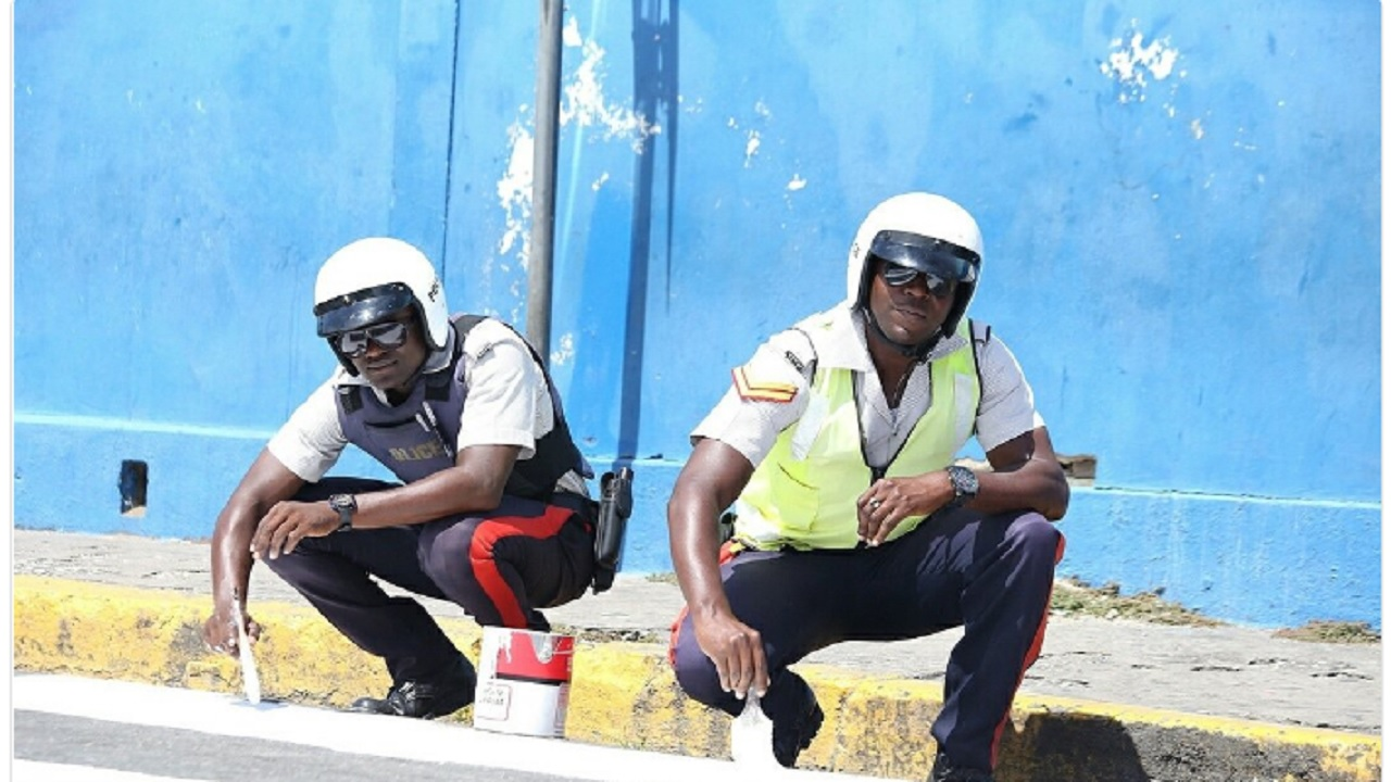 Constable Dwight Lewis (left) and Corporal Delvinan Douglas of the division were caught on camera carrying out painting work on a pedestrian crossing on White Church Street in the old capital.  (Photo: Office of the Prime Minister)