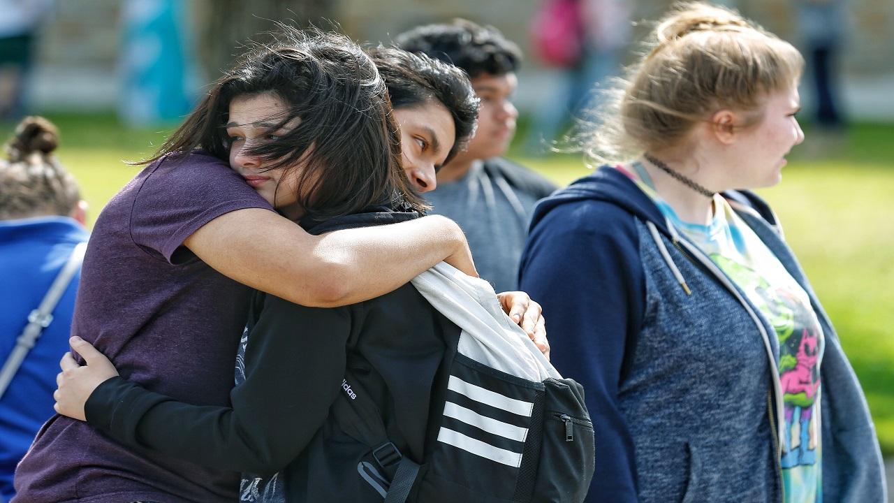 Santa Fe High School freshman Caitlyn Girouard, center, hugs her friend outside the Alamo Gym where students and parents wait to reunite following a shooting at Santa Fe High School Friday, May 18, 2018, in Santa Fe, Texas.