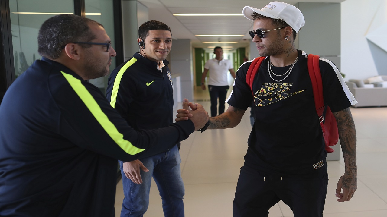 In this photo released by the Brazilian Football Confederation, Brazil's soccer player Neymar greets workers at the Granja Comary training center as he arrives to train in Teresopolis, Brazil, Monday, May 21, 2018. (Lucas Figueiredo/CBF via AP)