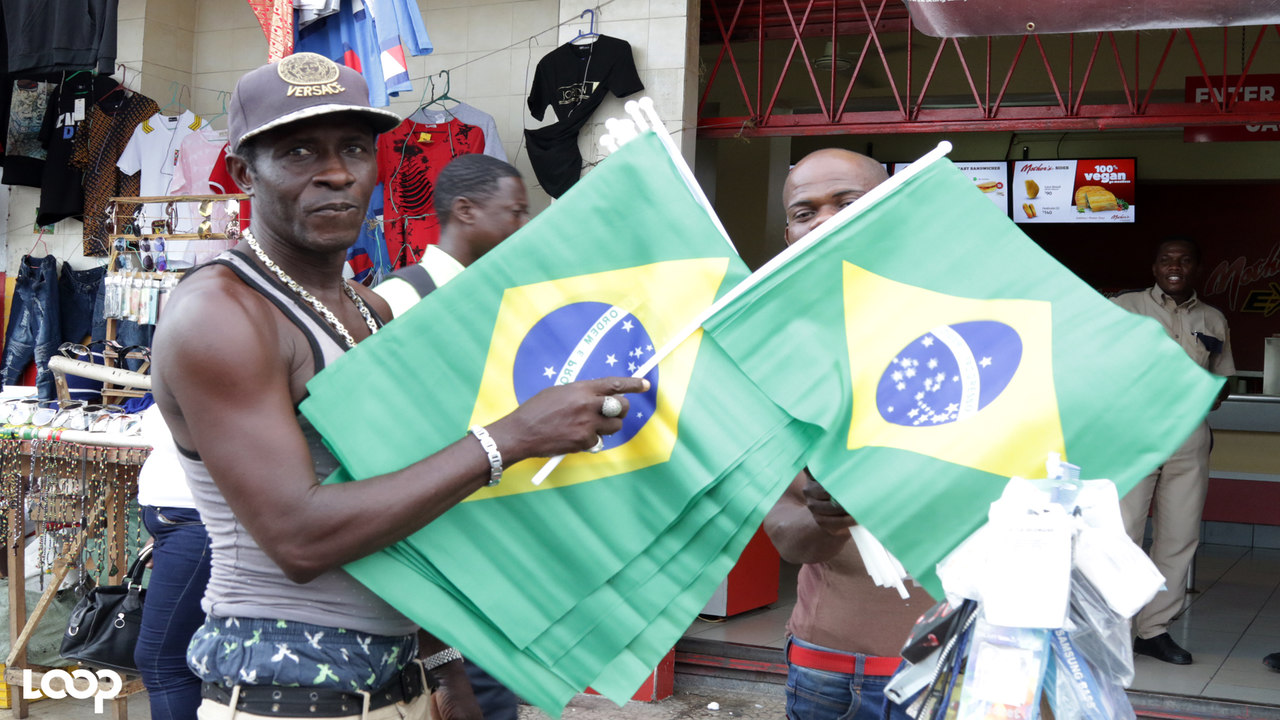 A vendor in downtown Kingston displays his collection of Brazilian flags, which have been selling like hot bread. (PHOTO: Ramon Lindsay)