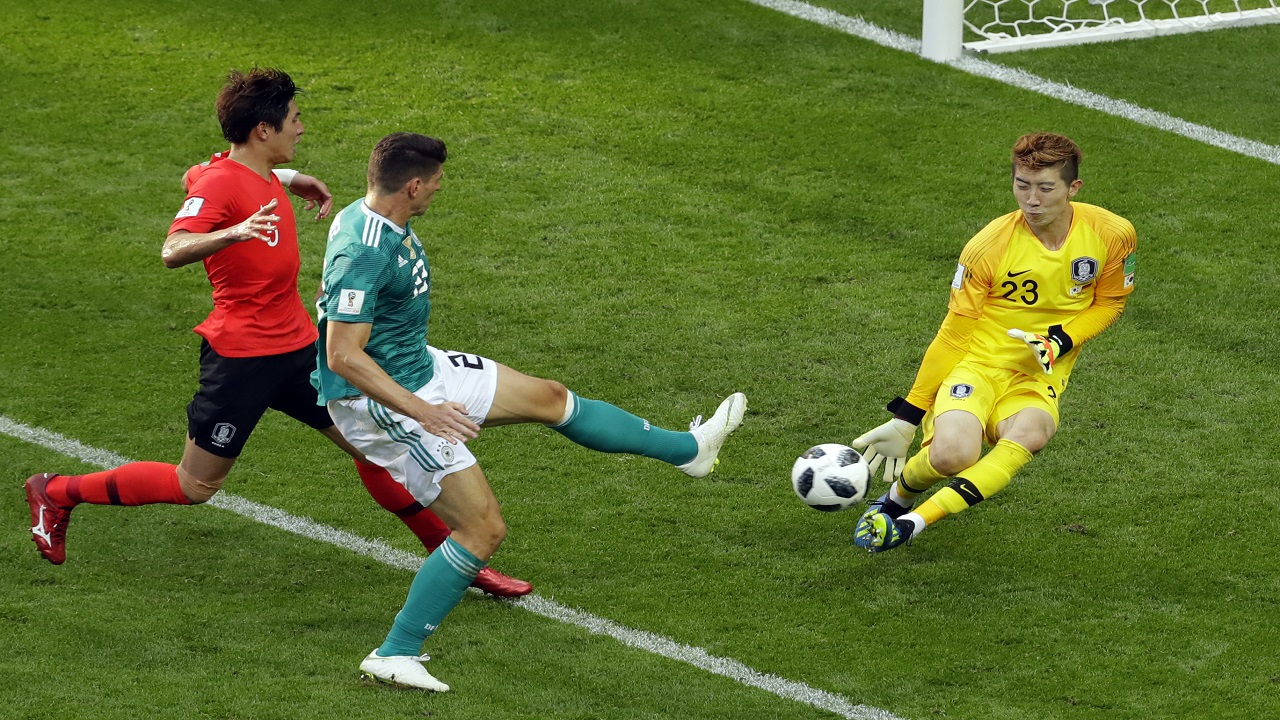 South Korea goalkeeper Jo Hyun-woo stops a shot from Germany's Mario Gomez, center, during the group F match at the 2018 football World Cup in the Kazan Arena in Kazan, Russia, Wednesday, June 27, 2018. (AP Photo/Sergei Grits).