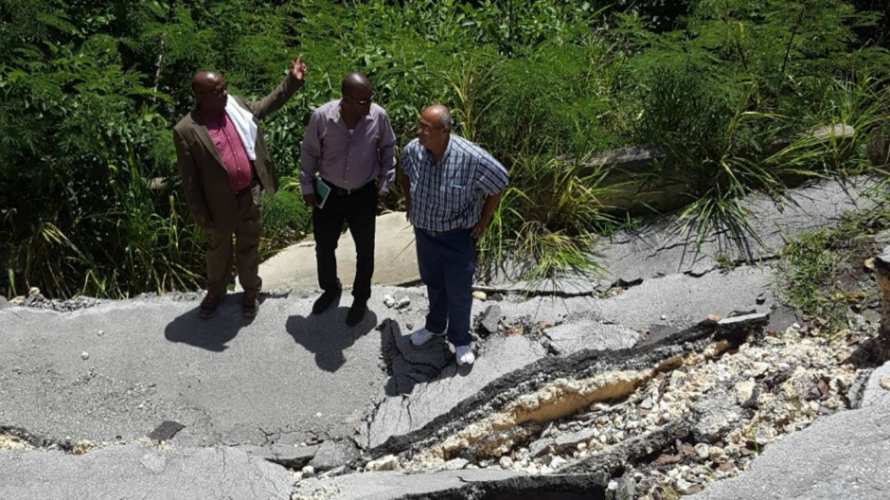 Minister of Housing, Lands and Rural Development, George Payne (left); Minister in the Ministry of Transport, Works and Maintenance, Peter Philips; and Minister of Transport, Works and Maintenance, Dr. William Duguid examining the collapsed road at Dark Hole, which connects St. Joseph and St. Andrew. (A. Husbands/BGIS)
