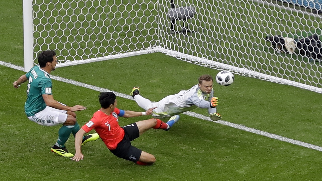 Germany goalkeeper Manuel Neuer dives for a save in front of South Korea's Son Heung-min, center, during the group F match at the 2018 football World Cup in the Kazan Arena in Kazan, Russia, Wednesday, June 27, 2018. (AP Photo/Sergei Grits)