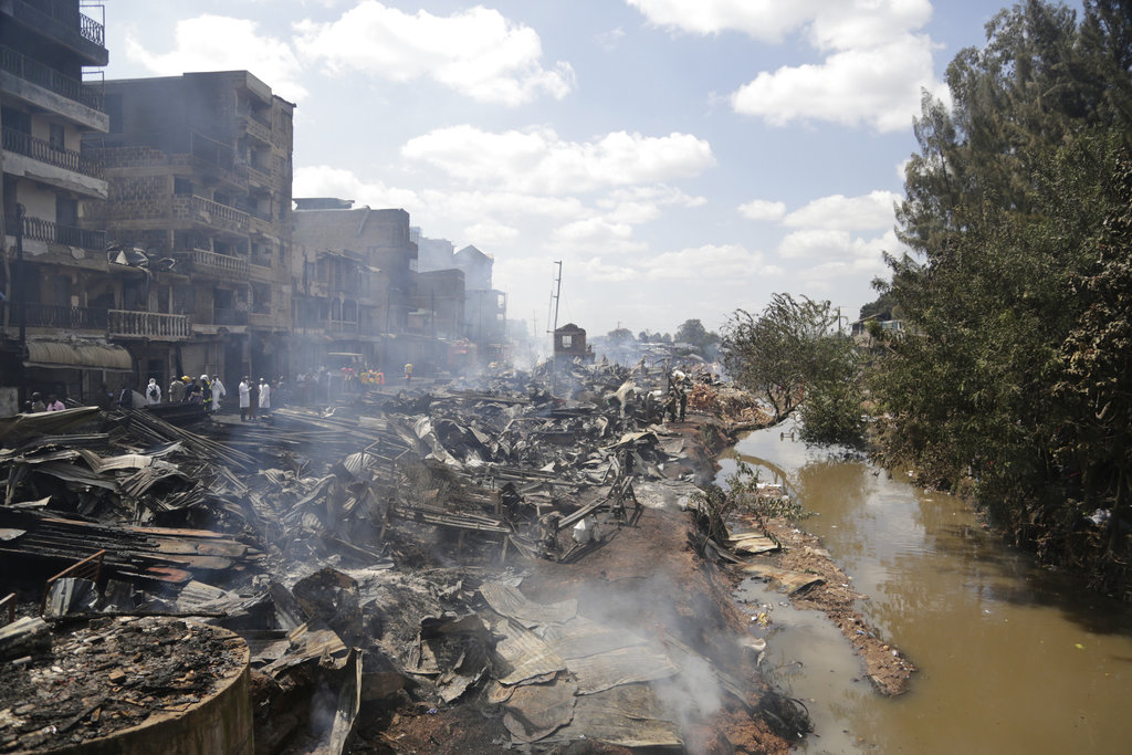 The scene of charred debris after a fire swept through a marketplace in Nairobi, Kenya, Thursday June 28, 2018. A fire swept one of Nairobi's largest open-air markets early Thursday, killing at least 15 people and sending 70 injured to hospitals, an official said, as traders who lived there struggled to wake their families and flee. (AP Photo/Khalil Senosi)