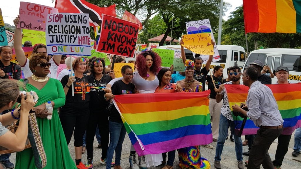 In this April 12, 2018 photo, LGBT+ supporters and members stand outside the Hall of Justice after the High Court decision which ruled in favour of human rights activist Jason Jones, declaring Trinidad and Tobago's sodomy laws as unconstitutional.