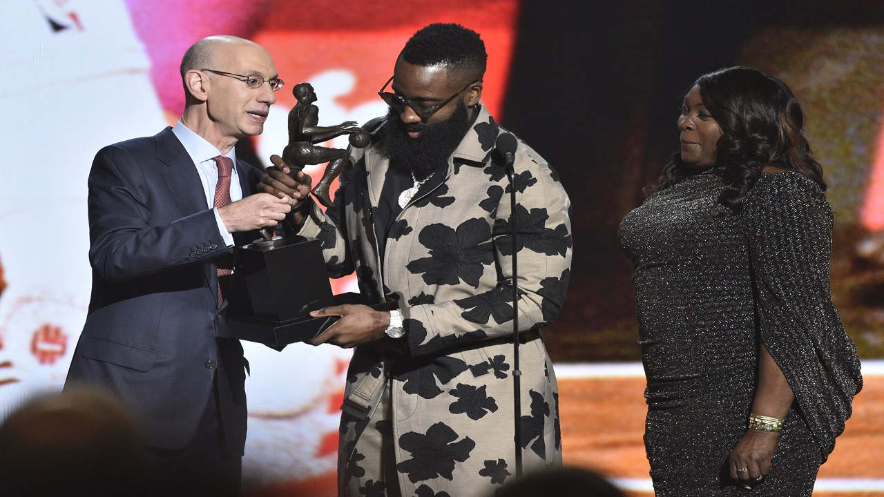NBA commissioner Adam Silver, from left, presents the most valuable player award to James Harden, of the Houston Rockets, as Harden's mother Monja Willis looks on at the NBA Awards on Monday, June 25, 2018, at the Barker Hangar in Santa Monica, Calif. (Photo by Chris Pizzello/Invision/AP)