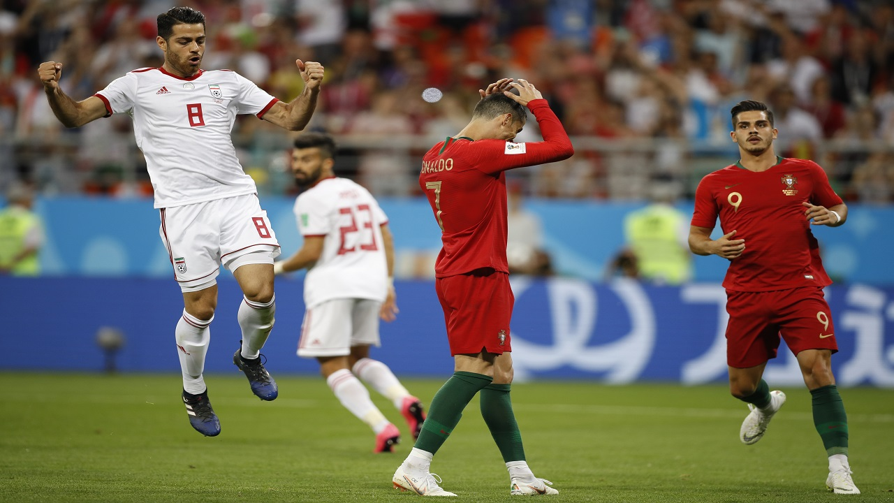 Portugal's Cristiano Ronaldo (centre) reacts after failing to score a penalty as Iran's Morteza Pouraliganji (left) celebrates during the group B match between Iran and Portugal at the 2018 World Cup at the Mordovia Arena in Saransk, Russia, Monday, June 25, 2018. (AP Photo/Francisco Seco)