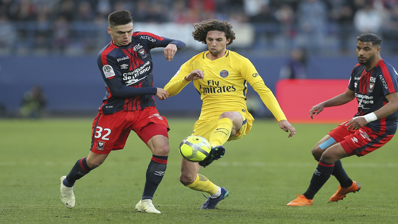 Adrien Rabiot of Paris Saint Germain challenges for the ball with Jessy Deminguet of Caen during their League One soccer match at the Michel d'Ornano stadium in Caen, western France.
