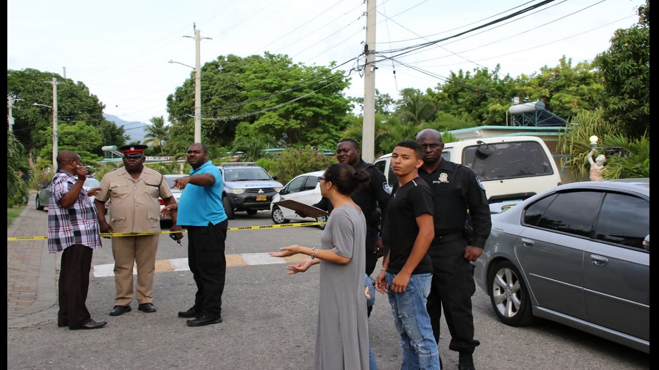 Police personnel and onlookers outside Mayfair Hotel in St Andrew on Sunday afternoon after businessman Brandon Murray was shot and killed outside the complex.