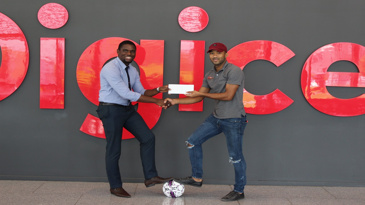 Mahaish Alexander (right) receives his plane ticket to Russia from Oldane Graham, NewCom's business intelligence and reporting analyst.